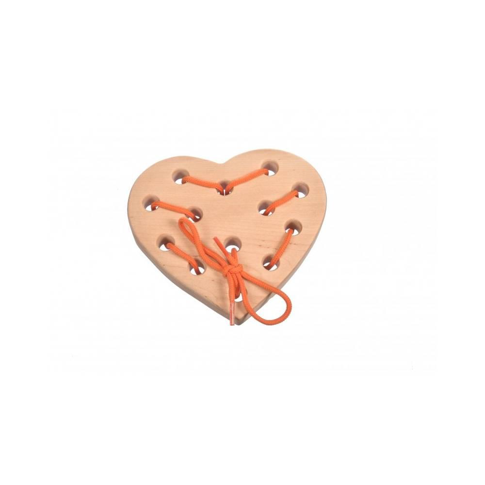 drewniane serduszko z dziurkami z przewleczoną przez nie sznurówka